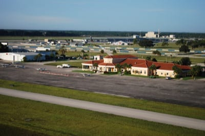 A view of the Sebring ramp on takeoff from runway 18; racetrack and grandstands are in the background.
