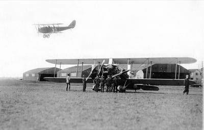 This Jenny, seen landing at Mineola Airport in Long Island, was flown by Richard Depew, who finished 22nd in the speed race and fifth in the handicap race. Seen on the ground is a new three-engined Eagle intended by Curtiss as a post-war airliner.