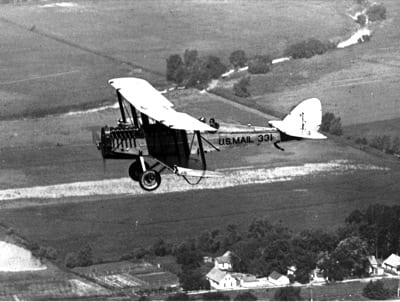 The DeHavilland DH-4B was the workhorse of the Air Mail Service, with more than 200 seeing service from 1919 to 1927. Modifications to the Army surplus planes included stronger landing gear, metal reinforcement of the longerons, and moving the pilot's position to the rear cockpit.