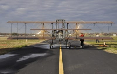"""Don Stroud and Rich Stepler fire up Wright """"B"""" Flyer No. 001 for its test flight at Stinson Airport in San Antonio, TX in preparation for tomorrow's Military Flight Centennial. WBF Operations Director Phil Beaudoin is in red jacket; crew chief Joe Tyler at right."""