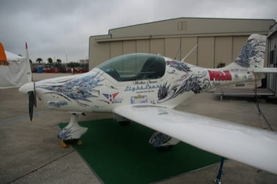 "The Peregrine starts out all white. Customers can chose a graphics package for the finish. This particular airplane was covered with advertisements for the sponsors of the Hansen/Scharle cross-country trip and what appeared to be feathers. ""There's a story behind that,"" Hansen laughed. ""The artist, Rob Winchester at TheInHouse, said that he'd donate the design if Matt allowed him to have free reign. At first we were scratching our heads when we saw the feathers, but it kind of grows on you. Rob  said 'it's different, but anybody can do a stripe'. The design has a lot of whirls and feathers on it. It looks like what you would imagine a bird would look like if it over-sped itself."""