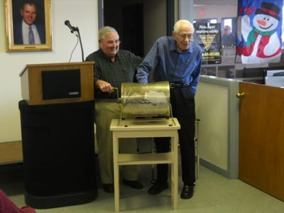 WinnAero Director Don Morrissey, left, assists retired Air Force Col. Robert Fortnam as he picks the winner of the organization's airplane raffle.  The winner of the Cessna 172G, Jane Williams of Florida, was chosen on January 5th at Laconia Municipal Airport in Gilford, NH.