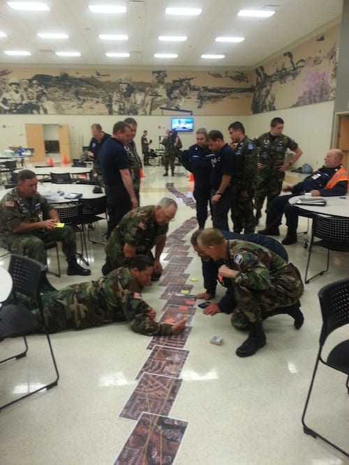 Members of Civil Air Patrol's Kansas and Oklahoma wings review a mosaic of images pasted together of the Moore tornado's track to help formulate a plan of attack for ground sorties in support of FEMA.