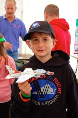 Kid proudly holds a model airplane he built