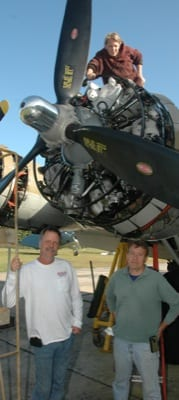 Mechanic Kaysha Raab performs a maintenance check on the B-17G as part of the scheduled yearly service for the Collings Foundation aircraft at American Aero Services. Company president Gary Norville (left) and Aero Services team member Vince Santorelly stand below.