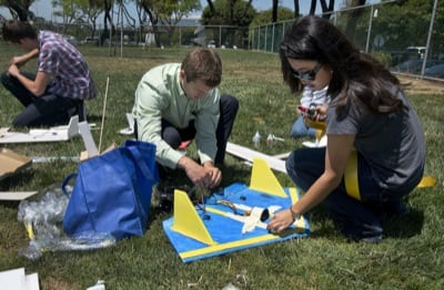 """Jeremy Alonso, a Northrop Grumman engineer, and Julia Tang, a senior at Redondo Beach (Calif.) Union High School, make final adjustments on a remotely controlled aircraft before its initial flight. Tang designed and built the aircraft as part of Northrop Grumman's High School Involvement Partnership (HIP), an award-winning mentoring program with local schools. HIP gives high school seniors the opportunity to obtain """"real world"""" work experience in a variety of disciplines at Northrop Grumman locations across the country."""