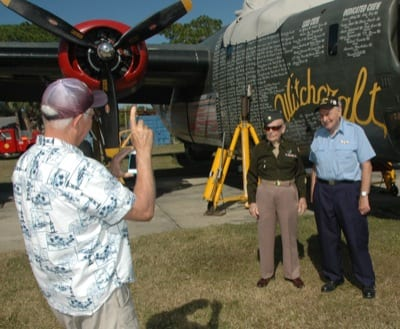 A visitor gets a photo of veterans Sam Mastrogiacomo and Joseph Reus (right) in front of the B-24 Liberator undergoing maintenance at American Aero.