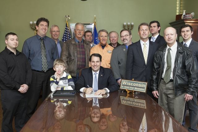 RAF Wisconsin Liaison Chuck Aldrian (in RAF orange) stands behind Governor Scott Walker as he signs the bill into law on April 17, 2014.