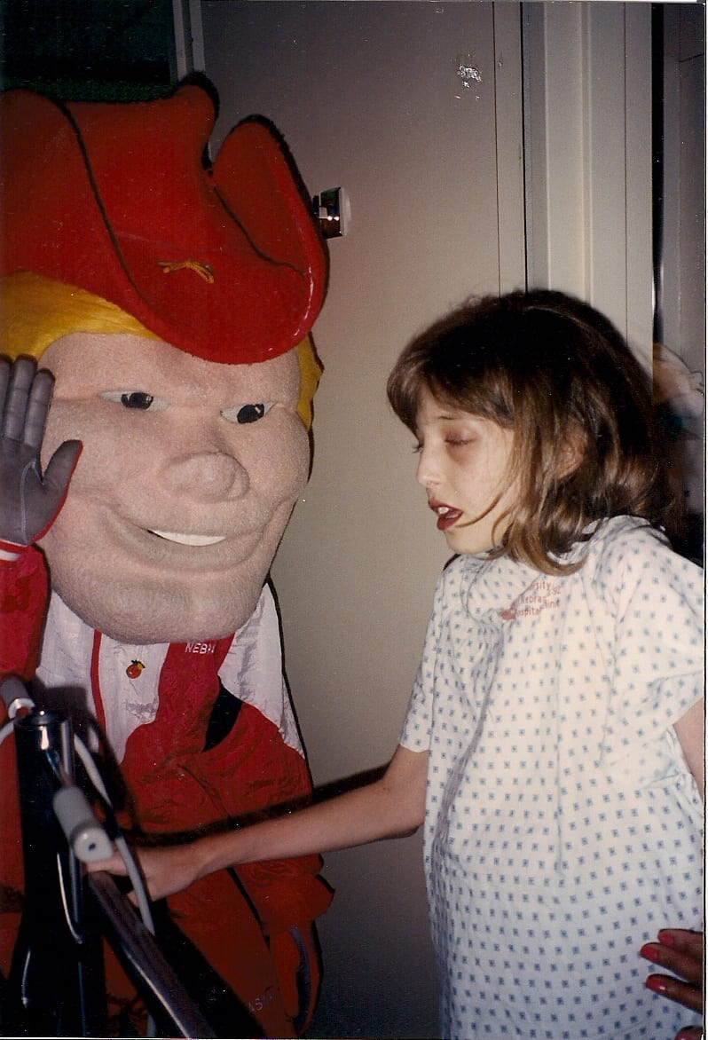 In 1994 at 12 years old with end-stage liver disease. This photo was taken while I was hospitalized in Omaha, waiting for my first transplant. A university hospital, the pediatric patients were visited by the Husker mascot