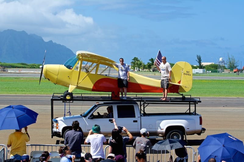 Hawaii local Alan Miller waves to the crowd after successfully landing his Aeronca Champ on the tiniest airport in the islands.