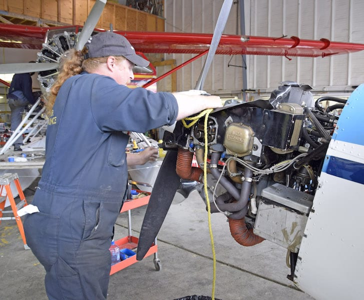 A&P Justin Rogers of Rodan Air Maintenance at Whitehorse prepares to use a length of rope to unstick an exhaust valve on N3245G.