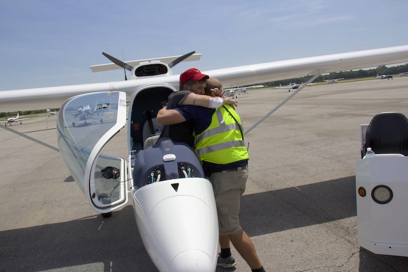 Paraplegic combat vet Chris Sullivan, Race 60, is lifted from his Sky Arrow LSA by a lineman from Vector Aviation following the Race for Heroes in the skies around Abbeville, Louisiana.  (Photo by Lisa F. Bentson)