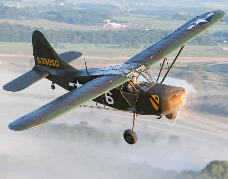 A Stinson L-5 on patrol during a misty Oshkosh morning