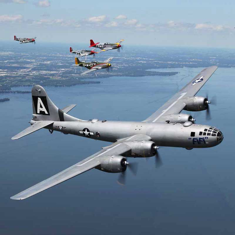 The B-29 FIFI, pride of the Commemorative Air Force fleet, is escorted to Oshkosh by four little friends, P-51 Mustangs