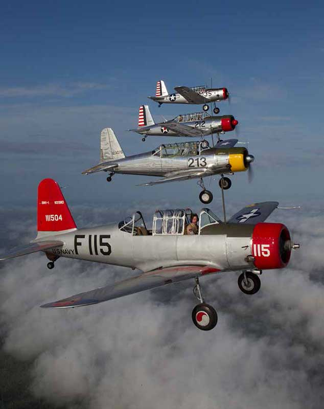 A flight of four Vultee BT-13 Vibrators stacked up on a photo shoot just above the cloud deck