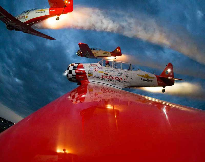 Smoke and noise: Take a ride on the T-6 wingtip of the famed AeroShell Aerobatic Team as they maneuver during a night air show