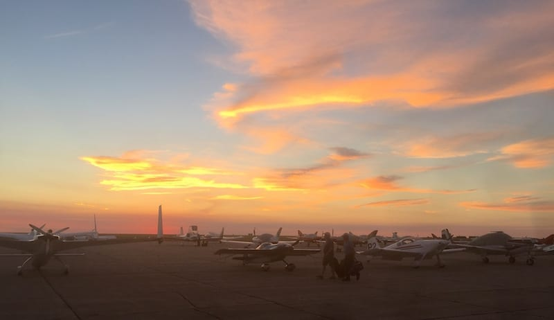 Racers make their way to their planes at dawn. The skies above the flight line before the start of the AirVenture Cup race suggested fine weather, but farther up the course conditions were IFR, prompting both a delay in launch and a mid-race stop for all 71 race planes at Owatonna, Illinois. (Photo by William E. Dubois)