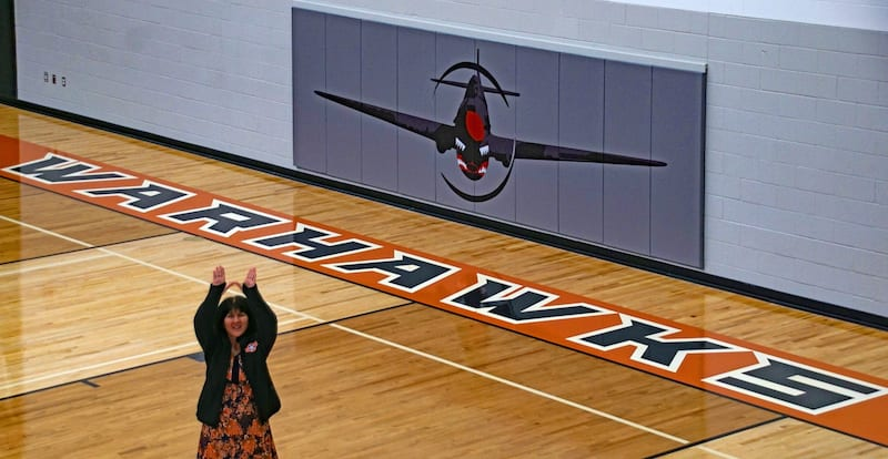 Ridgevue High principal Julie Yamamoto raises her hands to make the Warhawks 'W' sign in the gym where the namesake aircraft decorates the basketball court.