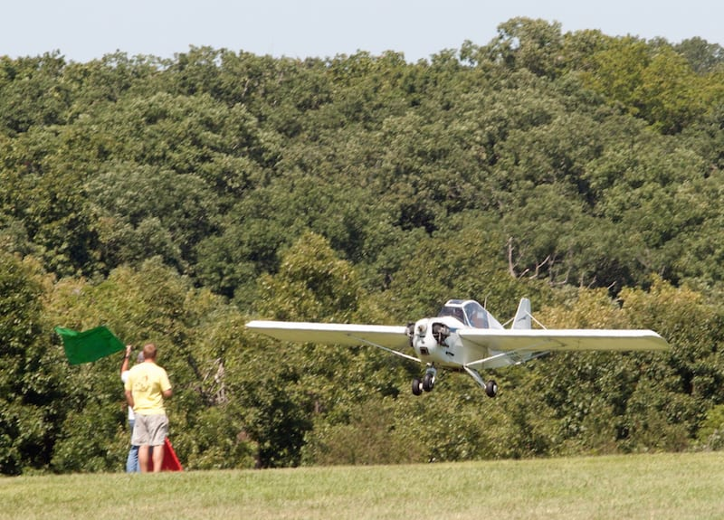 The flagman at Antique Airfield gives the Flut-R-Bug a green flag for landing