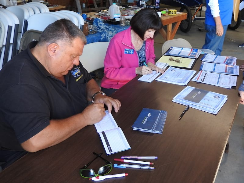 EAA Chapter 534 helicopter pilot Hans Gunter-Vosseler and EAA Chapter 534 President Jodie Soule worked hard to keep up with the Young Eagle paperwork in the hangar.
