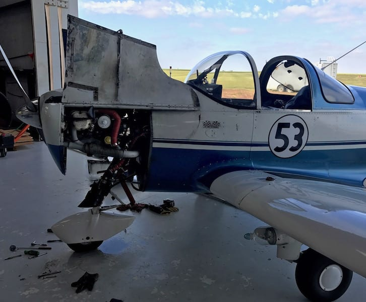 Not looking ready to race, Race 53 sits with her lower cowl and carburetor removed. The storm has passed, but the plane won't be flying anytime soon. Note the pool of fuel on the hangar floor. (Photo by William E. Dubois)