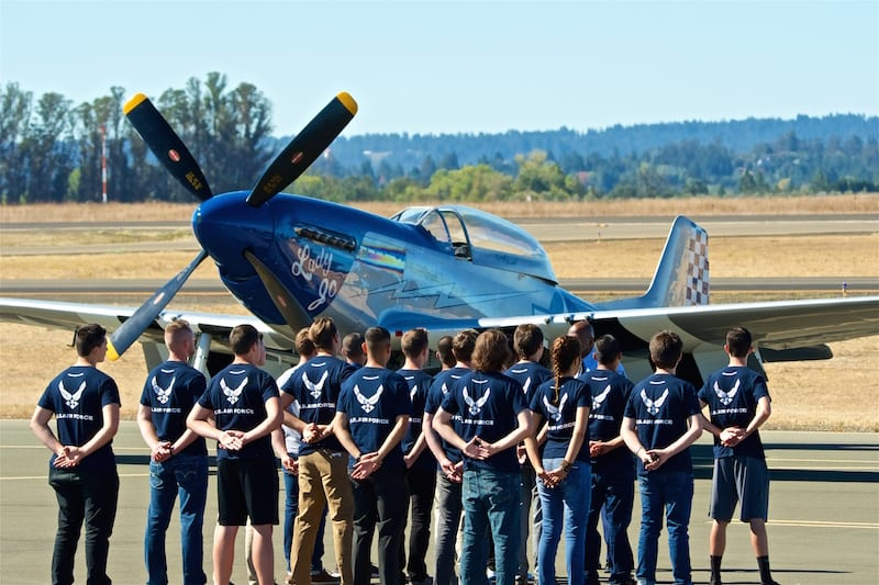 A group of new U.S. Air Force recruits prepares to take their Oath of Enlistment with a P-51 Mustang as a backdrop.