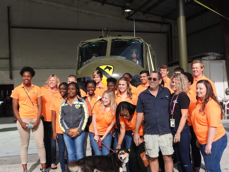 John and Mischele  Francis, owners of the Flying Colors Paint Shop, have their picture taken with the students in front of a recently painted Huey helicopter about to become a part of a Veterans Memorial on display in Leesburg, Florida.