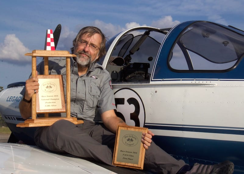 """Brand new National (Silver) Champion air racer William E. Dubois displays his season-end trophies with the plane that made it all possible: The 69-year-old Ercoupe N3975H, a.k.a. Race 53 (known to family and friends as """"Tessie""""). The high final ranking of the Ercoupe this season is proof positive that the League's motto, """"Racing for the rest of us"""" is valid. (Photo by Lisa F. Bentson)"""