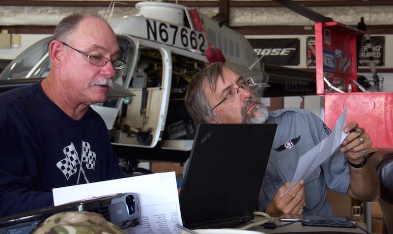 """Crunching the math, League Chairman Mike Thompson and air racer William E. Dubois try to make sense out of """"triple-checked"""" math that put the Ercoupe at an improbably fast race speed. In the end, a simple handwriting error was suspected—a quickly drawn nine resembling a zero when the finish time was recorded. Racers use in-cockpit data recorders—or even simple stopwatches—to protect their reputations from just such rare occurrences. Dubois was able to check his CloudAhoy app to ensure that all his turns were legal. They were, but barely. Race 53 corkscrewed tightly around all the virtual pylons. (Photo by Lisa F. Bentson)"""