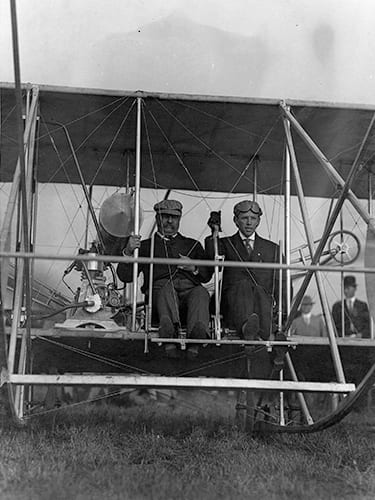 Former President Theodore Roosevelt and pilot Arch Hoxsey preparing for take-off for Roosevelt's first airplane ride. International Aviation Meet, Kinloch Field. 11 October 1910. Photograph by David M. Boyd, 1910. Missouri History Museum Photographs and Prints Collections. Aviation. n07161.